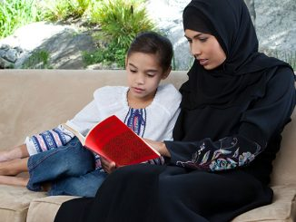 A young Arab woman, wearing a traditional black hijab, sitting next to her 8-9 year old daughter and reading a book together