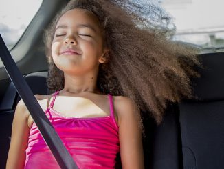 Waist-up view of a 6-7 year old mixed race girl sitting in the back seat of a car and enjoying the wind blowing in her hair